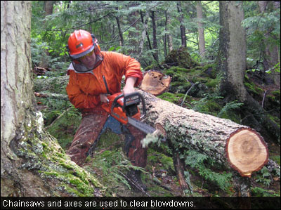 Chainsaws and axes are used to clear blowdowns.